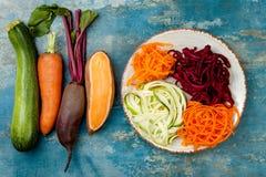 夏南瓜、红萝卜、白薯和甜菜根面条在板材 顶视图,顶上 蓝色土气背景 免版税库存图片
