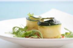 夏南瓜和芝麻菜开胃菜在一块板材在一蓝色backgrou 免版税库存图片