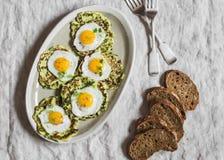 夏南瓜油炸馅饼用煎鹌鹑蛋 可口早餐或快餐在一张灰色桌上,顶视图 免版税图库摄影