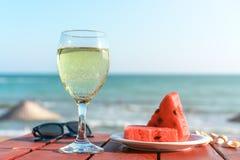 夏天、一以海为背景的杯香槟和果子 库存照片