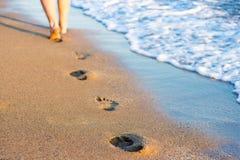 夏天、旅行和假期概念-腿,脚印在sa中 免版税库存图片