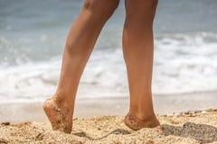 夏天、海滩、休闲和身体局部概念-妇女腿特写镜头在海岸的 免版税库存图片