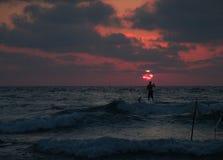 夏天一个海滩的日落视图在与一个唯一一口冲浪者剪影的多云天空下 免版税图库摄影