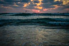 夏天一个海滩的日落视图在剧烈的多云天空下 免版税库存照片