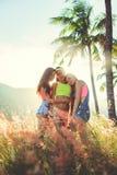 夏天三个俏丽的女朋友生活方式画象获得在空气的乐趣在棕榈和海附近 妇女拥抱 晴朗 免版税库存照片
