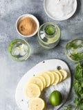 夏天与冰在两块凸起的玻璃,在一点白色板材的糖,切片的柑橘柠檬水在一个陶瓷白板的柑橘和 库存图片