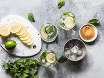 夏天与冰在两块凸起的玻璃,在一点白色板材的糖,切片的柑橘柠檬水在一个陶瓷白板的柑橘和 免版税图库摄影