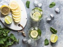 夏天与冰在两块凸起的玻璃,在一点白色板材的糖,切片的柑橘柠檬水在一个陶瓷白板的柑橘和 库存照片