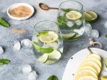夏天与冰在两块凸起的玻璃,在一点白色板材的糖,切片的柑橘柠檬水在一个陶瓷白板的柑橘  图库摄影