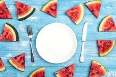 夏天与利器和切的西瓜的桌设置在蓝色木桌上 免版税库存图片