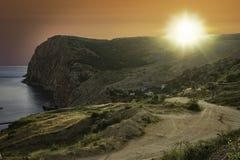 夏天与小山和房子的海风景晚上日落和明亮的太阳背景的  免版税库存照片