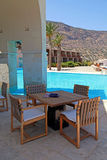 夏天与水池和室外家具(希腊)的旅馆大阳台 免版税库存照片