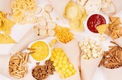 夏天乐趣快餐-在工艺的不同的嘎吱咬嚼的快餐裱糊锥体和辣调味汁和咖喱汁在碗在软的白木委员会 库存照片