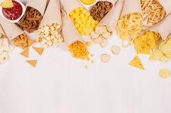 夏天乐趣快餐-在工艺的不同的嘎吱咬嚼的快餐裱糊锥体和辣调味汁和咖喱汁在碗当装饰边界 库存照片