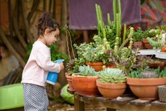 夏天乐趣:一点美女浇灌的庭院 免版税库存图片