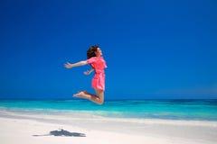 夏天享受 愉快的少妇跳跃在海的,浅黑肤色的男人 免版税库存图片