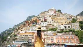 夏天休假在意大利 年轻女人在背景的波西塔诺村庄,阿马尔菲海岸,意大利 股票视频