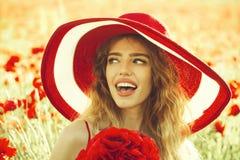 夏天休息时髦的女人摆在 罂粟种子的领域的女孩在减速火箭的帽子的 免版税库存图片