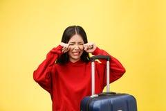 夏天便服的让烦恼的旅游妇女在橙黄背景的头上坐手提箱把手放 图库摄影