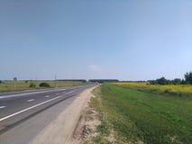 夏天俄国领域、路,蓝天,绿色和黄色草 免版税图库摄影
