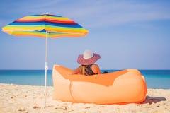 夏天俏丽的女孩生活方式画象坐在海滩的橙色可膨胀的沙发热带海岛 ?? 免版税图库摄影