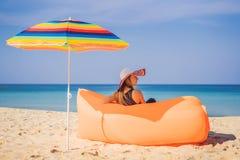 夏天俏丽的女孩生活方式画象坐在海滩的橙色可膨胀的沙发热带海岛 ?? 免版税库存照片