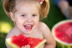 夏天健康食物 夏天健康食物 吃西瓜的愉快的微笑的孩子在公园 逗人喜爱的小女孩特写镜头画象  库存图片