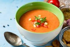 夏天冷的汤gazpacho用荷兰芹和菜在蓝色具体背景 免版税库存图片