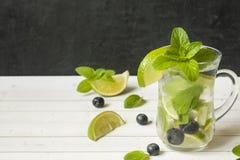夏天刷新的与石灰新鲜薄荷蓝莓冰的饮料柠檬水或鸡尾酒Mojito 轻的桌,黑暗的墙壁 库存照片