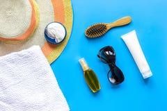 夏天化妆用品有保护奶油和帽子蓝色背景顶视图 图库摄影