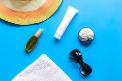 夏天化妆用品有保护奶油和帽子蓝色背景顶视图 库存照片