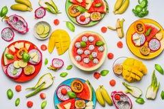 夏天各种各样的五颜六色的切的热带水果和莓果平的位置在板材和碗在白色背景 免版税库存照片
