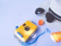 夏天和旅行辅助部件平的位置视图  防水黄色照相机,帽子,太阳镜, sunblock奶油色保护 图库摄影