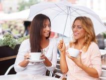 夏天咖啡馆的两个美丽的女孩 免版税库存照片