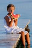 夏天喜悦,吃在海滩的可爱的女孩新鲜的西瓜 免版税库存照片