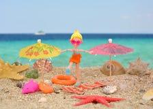 夏天喜悦- polly有口袋女孩的玩偶在海滩的好时间 库存图片