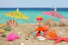 夏天喜悦- polly有口袋女孩的玩偶在海滩的好时间 库存照片