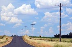 夏天在一条乡下公路的热阴霾通过农田 库存图片