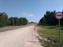 夏天在俄国村庄,路,蓝天,绿色树 图库摄影