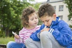 夏天在公园一个小卷发的男孩显示他的坏胳膊a 免版税图库摄影