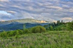 夏天在山的早晨薄雾,阳光通过低云 库存图片