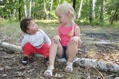 夏天在桦树日志的森林坐两个妹 免版税库存图片