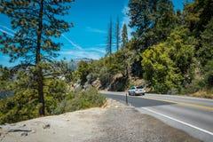 夏天在美国自然公园的汽车游览 在高速公路的家用汽车在优胜美地国家公园 免版税库存图片