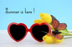 夏天在这里与红色心脏形状太阳镜的概念 库存照片