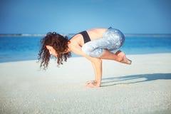 夏天在马尔代夫瑜伽游览, Bakasana乌鸦起重机姿势一个美丽的金黄海滩的瑜伽会议  免版税库存照片