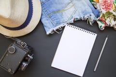 夏天套妇女` s衣裳 有牛仔布短裤、帽子、葡萄酒照相机和笔记本的女性女衬衫 顶视图 免版税图库摄影