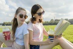 夏天好日子,两个女朋友少年坐绿色草坪,饮料鸡尾酒,谈话,读的书,笑,获得乐趣,金黄小时 图库摄影