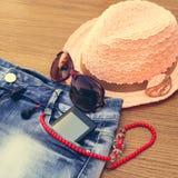 夏天妇女的辅助部件太阳镜,小珠,短裤,手机,耳机,太阳帽子 免版税库存照片
