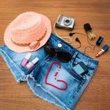 夏天妇女的辅助部件:红色太阳镜,小珠,牛仔布短缺,手机,耳机,太阳帽子,照相机,指甲油, 免版税图库摄影