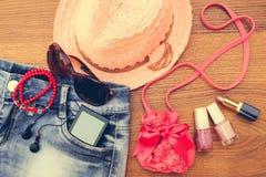 夏天妇女` s辅助部件太阳镜,小珠,牛仔布短缺,手机,耳机,太阳帽子,提包,唇膏,指甲油 免版税库存图片